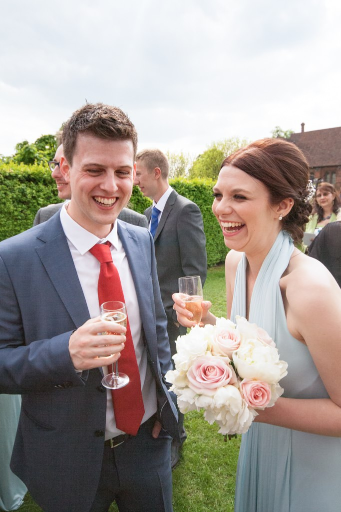 Hertfordshire Wedding Photographer - bridesmaid laughing with guest