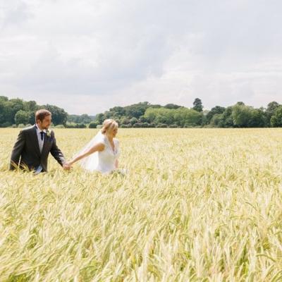 Norfolk wedding photographer – bride and groom walking through field